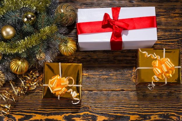 Boże narodzenie tło z ozdobnymi prezentami przewiązanymi wstążką i kokardkami oraz złotymi bombkami ułożonymi na gałęzi jodły na drewnianym tle widzianym z góry