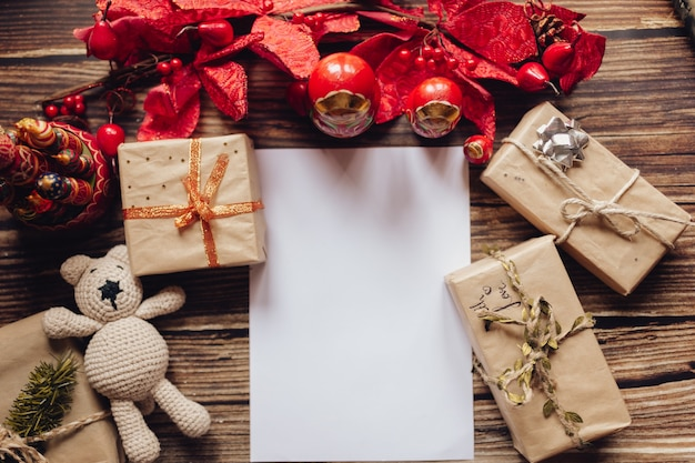Boże narodzenie tło z papieru kraft, pudełko, ręcznie robione zabawki świąteczne. widok z góry na drewniane biurko. ozdoba i prezent na boże narodzenie. list świętego mikołaja.