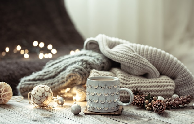 Boże narodzenie tło z piękną filiżanką, dzianinowym elementem i dekoracyjnymi detalami na rozmytym tle z bokeh.