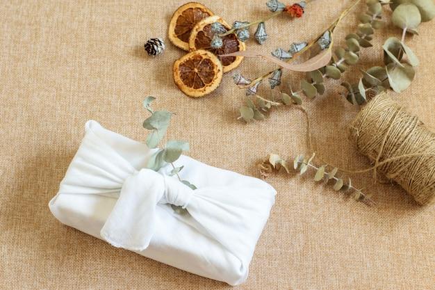 Boże narodzenie tło z pudełkiem w stylu furoshiki, przyjazne dla środowiska proste liny, gałęzie eukaliptusa. boże narodzenie, alternatywne prezenty zawinięte w ubrania, japońska tradycja.