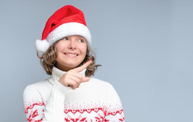 Boże narodzenie tło z uśmiechniętą nastolatką w kapeluszu świętego mikołaja z palcem wskazującym