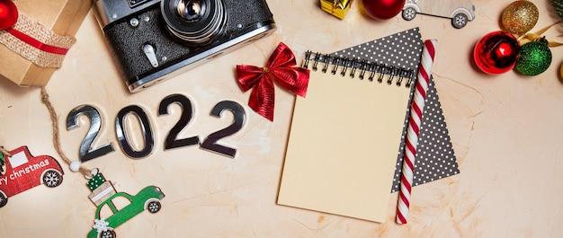 Boże narodzenie tło z zabawkami gałęzie choinkowe numery 2022 aparat i notatnik