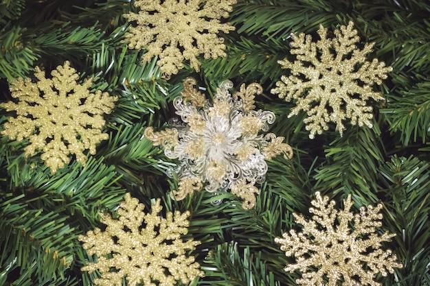 Boże narodzenie tło z złote płatki śniegu na choince.
