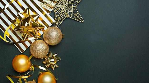Boże narodzenie tło z złotych kulek, serpentyn na ciemnym tle. kartka świąteczna. skopiuj miejsce.