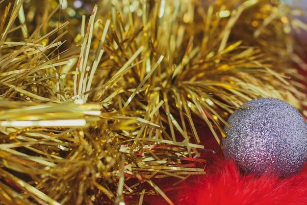 Boże narodzenie tło złoty blichtr i boże narodzenie srebrna piłka na czerwonym futrze. puszyste futerko z długim włosiem. selektywne skupienie płytkie na piłce.