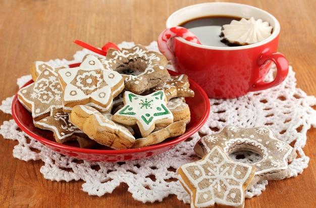 Boże narodzenie traktuje na talerz i filiżankę kawy na drewnianym stole z bliska