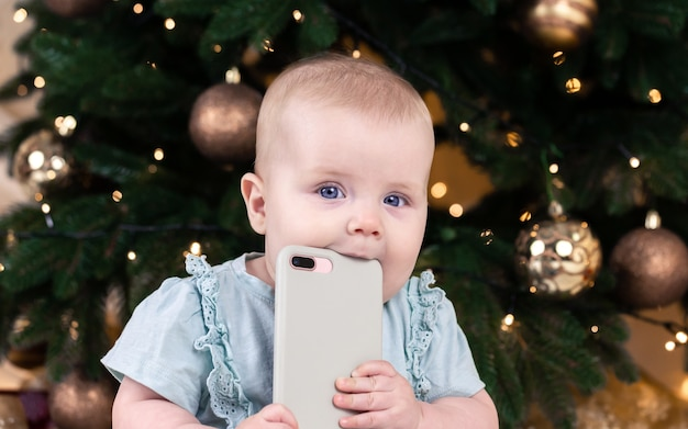 Boże narodzenie urocza mała dziewczynka rozmawia przez telefon. portret dziecka dziecka na tle choinki. boże narodzenie ładny maluch.