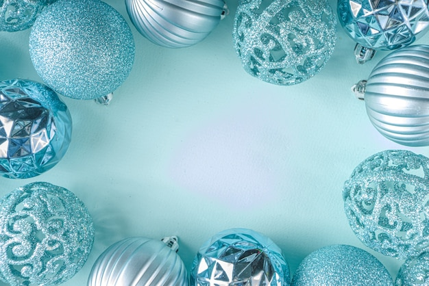 Boże narodzenie uroczysty transparent, tło. monochromatyczny układ płaski z różnymi niebieskimi bombkami dekoracyjnymi na jasnoniebieskim tle