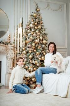 Boże narodzenie w domu syn i mama i pies pod drzewem chłopiec i kobieta bawią się ze zwierzęciem...