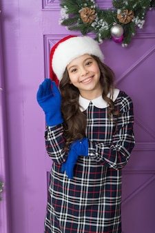 Boże narodzenie w domu. szczęśliwego nowego roku dla ciebie. wesoła dziewczyna w santa claus kapelusz i rękawiczki. aktywność na ferie zimowe. zakupy sezonowe. ostatnie przygotowanie małej elfki. stylowe dziecko udekoruje dom.