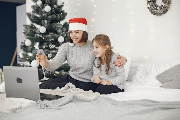Boże narodzenie w internecie. obchody bożego narodzenia w nowym roku w kwarantannie na koronawirusa. impreza online. matka z córką.