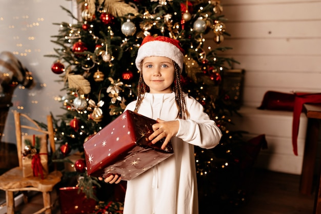 Boże narodzenie, wesołe dziecko w świątecznej czapce z prezentem stwarzającym nad choinką