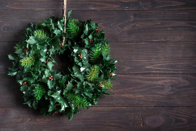 Boże narodzenie wieniec ozdoba zielonych liści i jagód ostrokrzew roślina na białym tle na ciemny drewniany. copyspace