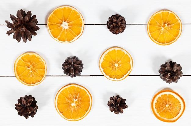 Boże narodzenie wzór z szyszek jodły i suszone plastry pomarańczy na białym tle drewnianych.