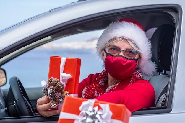 Boże narodzenie z koronawirusem. starsza kobieta w czapce mikołaja i masce medycznej, aby uniknąć zakażenia koronawirusem, jeździ samochodem, by dostarczyć do domu prezenty świąteczne.