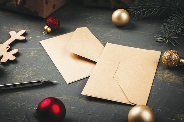 Boże narodzenie z listem, kopertą i piórem w otoczeniu sezonowych dekoracji