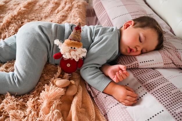 Boże narodzenie zabawka na tle śpiącego chłopca