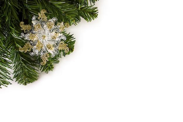 Boże narodzenie zabawka śnieżynka na choince. piękne zbliżenie płatka śniegu i inne ozdoby na choince ze światłami.