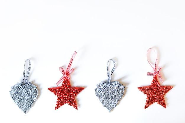 Boże narodzenie zabawki dekoracyjne czerwone gwiazdki i srebrne serca z wstążkami na białym tle. koncepcja nowego roku