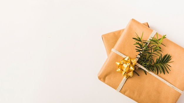 Boże narodzenie zapakowane prezenty z gałęzi jodły i złoty łuk