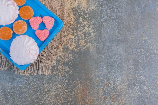 Boże narodzenie zephyr z galaretkami cukierki na niebieskim talerzu. wysokiej jakości zdjęcie