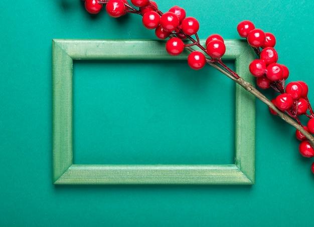 Boże narodzenie zielone tło z ramką z miejscem na tekst lub skopiuj miejsce z gałązką czerwonych jagód lub kaliny.