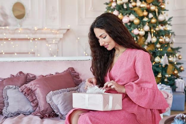 Boże narodzenie, zima, koncepcja szczęścia - uśmiechnięta kobieta w różowej sukience