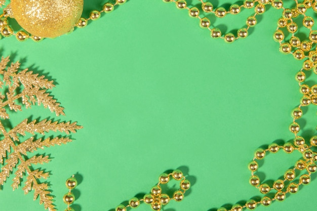 Boże narodzenie złota dekoracja tworząca ramkę na stylowym zielonym tle świąteczne, widok z góry.