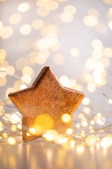 Boże narodzenie złote tło bokeh z ozdobną gwiazdą. boże narodzenie złote gwiazdy. boże narodzenie wzór. tło w kolorze szarym. - wizerunek
