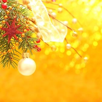 Boże narodzenie - złote tło z wystrojem, wstążką i piłką