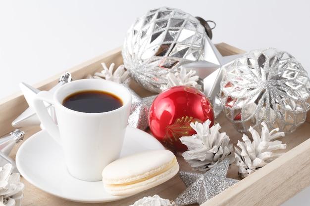 Bożenarodzeniowa dekoracja i mała filiżanka kawy na bielu