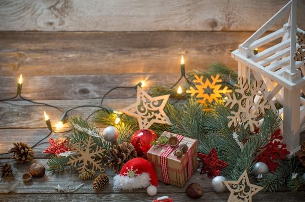 Bożenarodzeniowa dekoracja z białym lampionem na drewnianym tle