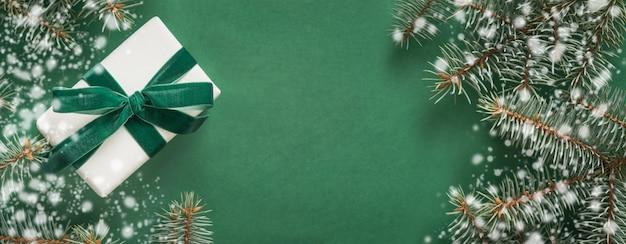 Bożenarodzeniowa dekoracja z xmas drzewem i białym prezentem na zielonym tle. wesołych świąt bożego narodzenia. zimowe wakacje.