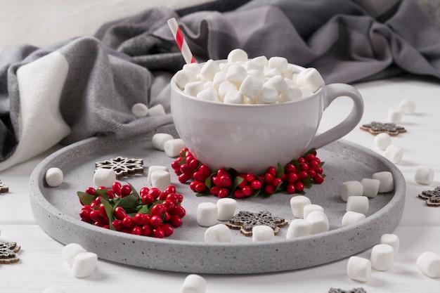 Bożenarodzeniowa gorąca czekolada lub kawa z marshmallow na białym drewnianym stole z boże narodzenie dekoracjami