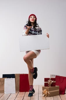 Bożenarodzeniowa kobieta trzyma dużego biel karty copyspace