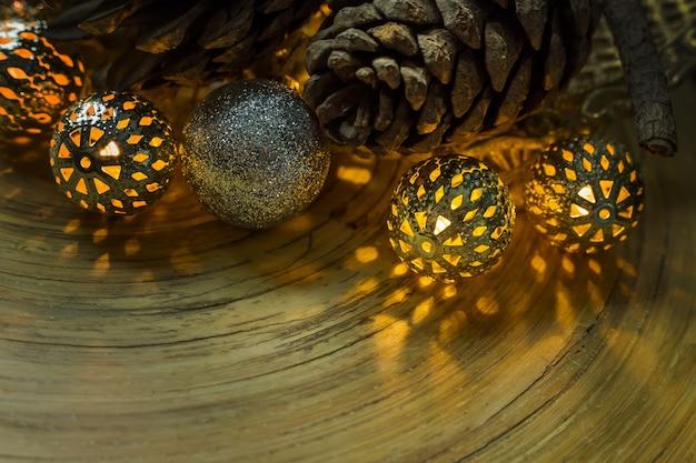 Bożenarodzeniowa piłka i sosna konusujemy na drewnianym tle.