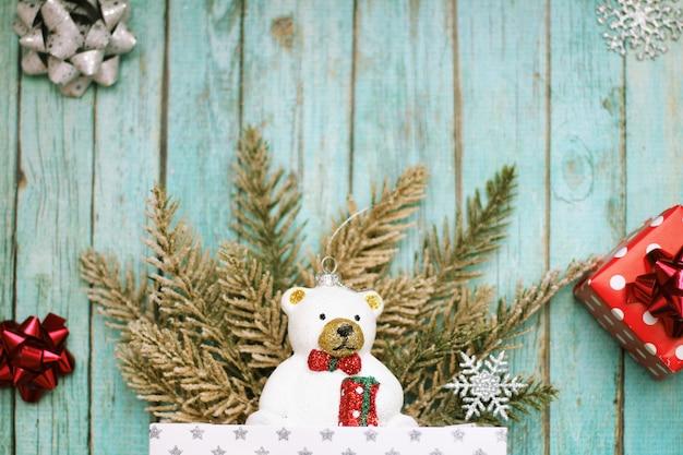 Bożenarodzeniowa zabawka niedźwiedź polarny, czerwone pudełko, łuki i sztuczne świerkowe gałęzie na niebieskim tle drewnianych.