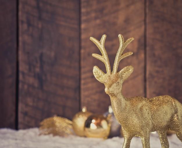 Bożenarodzeniowa złocista reniferowa dekoracja z drewnianym tłem