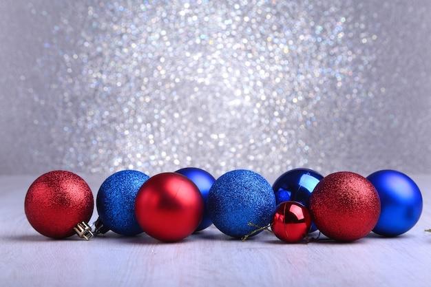 Bożenarodzeniowe czerwone i błękitne piłki odizolowywać na srebrze