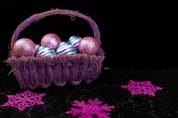 Bożenarodzeniowe piłki w purpurowym koszu na czarnym tle. dekoracyjne płatki śniegu