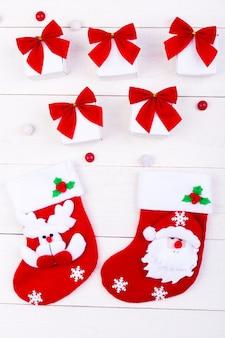 Bożenarodzeniowe skarpety i prezenty, białe małe pudełka z czerwoną kokardą i cukierki na białym drewnianym tle.