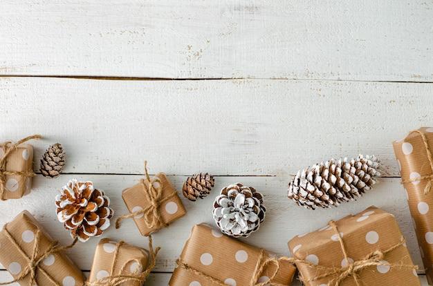 Bożenarodzeniowe świąteczne decotrations z prezentów pudełkami i rożkami na białym drewnianym tle