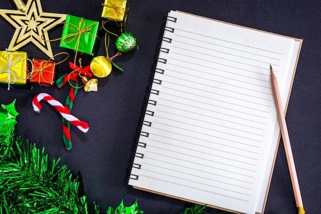 Bożenarodzeniowe świąteczne dekoracje z pustym notatnikiem i ołówkiem na czarnym papierowym tle, ne