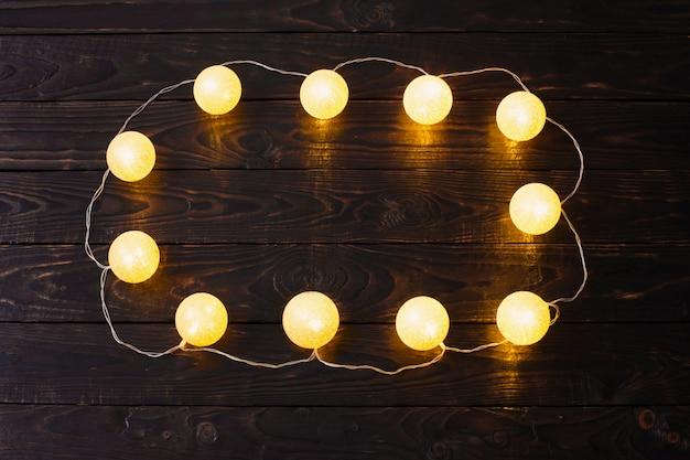 Bożenarodzeniowe złote światła na ciemnym drewnie