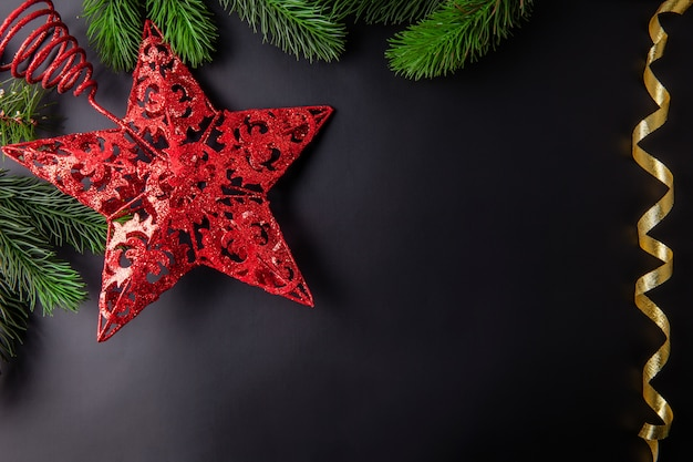 Bożenarodzeniowej dekoraci czarny tło z treetop czerwieni gwiazdą