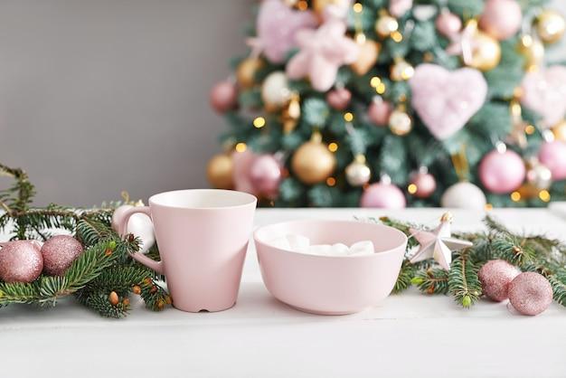 Bożenarodzeniowi cukierki na tle choinka. różowe ozdoby świąteczne. szczęśliwego nowego roku! tradycyjny deser noworoczny. skopiuj miejsce