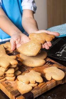 Bożenarodzeniowi piernikowi ciastka i dzieciak ręki.