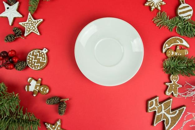 Bożenarodzeniowi piernikowi ciastka z nowy rok dekoracjami na czerwonym tle z talerzem. wakacje, święta, deser, jedzenie nowego roku, koncepcja elementów projektu