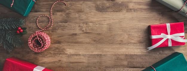 Bożenarodzeniowi prezentów pudełka na drewnianym stołowym sztandaru tle