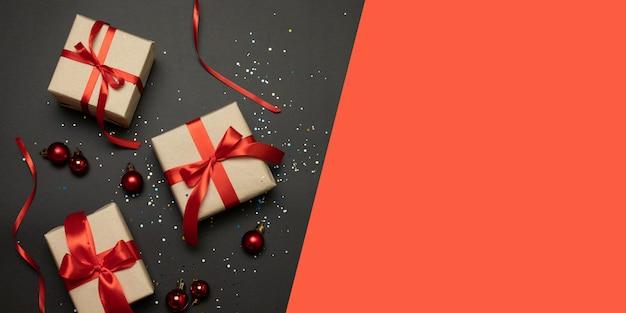 Bożenarodzeniowi prezenty, iglaste gałąź, czerwone i złociste dekoracje na ciemnym tle.